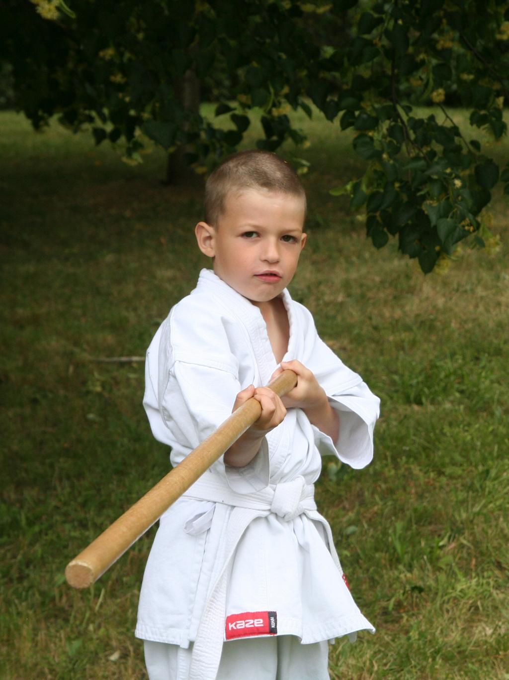 malý aikido bojovník trénuje so zbraňou